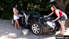 Beautiful girls wash an expensive car