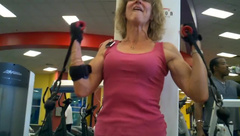 old fit woman exhausts herself training arms in gym
